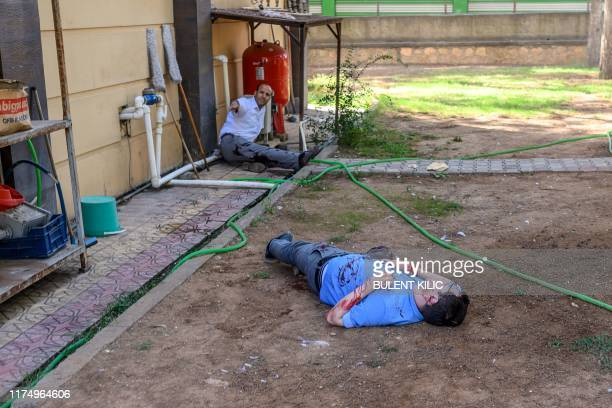 Graphic content / A severely injured officer lies on the ground next to another injured officer in the garden of a Turkish government building in...