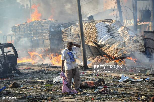 Graphic content / A Somali man reacts next to a dead body on the site where a car bomb exploded at the center of Mogadishu on October 14 2017 More...