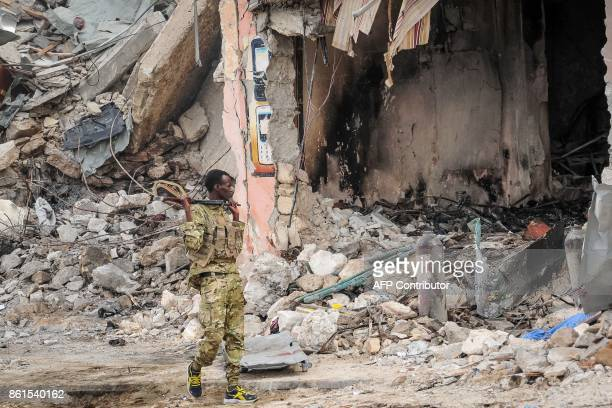 Graphic content / A Somali soldier patrols on the scene of the explosion of a truck bomb in the centre of Mogadishu on October 15 2017 A truck bomb...