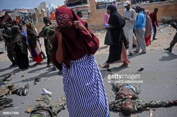 Graphic content / A Somali woman stands near the bodies of three suspected Shabaab fighters who were shot dead after exchanging fire with security...