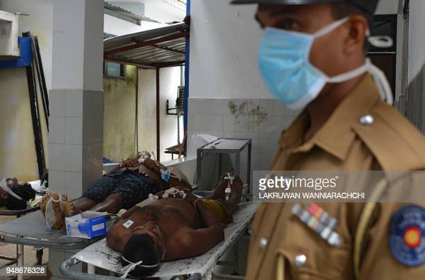 Graphic content / A Sri Lankan policeman keeps vigil around the dead bodies of workers of a rubber processing factory following a toxic gas leak at...