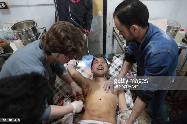 Graphic content / A Syrian boy receives treatment at a makeshift clinic following reported air strikes by government forces in the rebelheld town of...