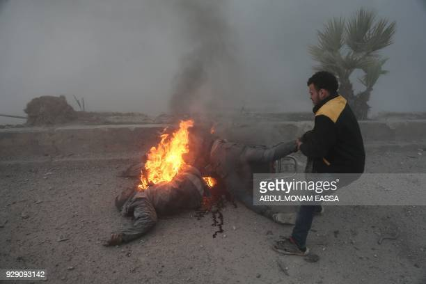 Graphic content / A Syrian civil defence volunteer tries to rescue two men engulfed by fire during bombardment of the rebelheld town of Hamouria in...