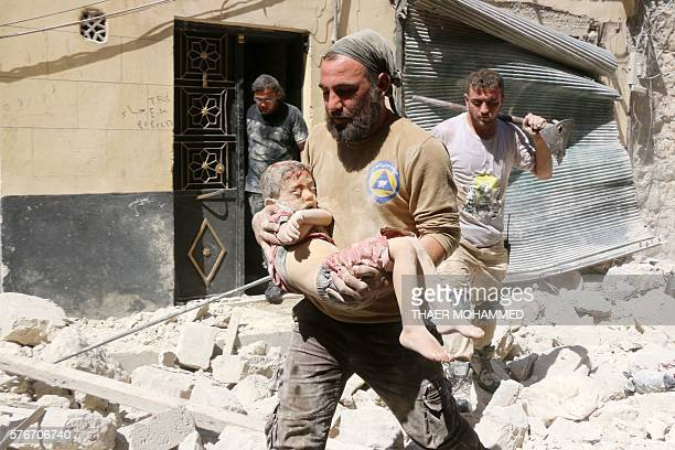 Graphic content / A Syrian civil defence worker carries the body of a child following reported air strikes on July 17 2016 in the rebelcontrolled...