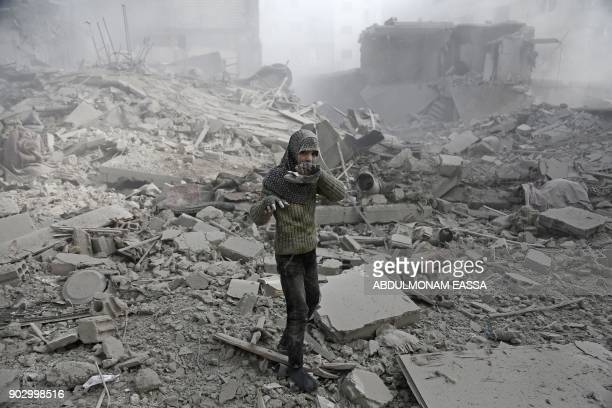 Graphic content / A Syrian girl appears from the rubble holding her shoe following an air strike on Hamouria in the besieged rebelheld Eastern Ghouta...