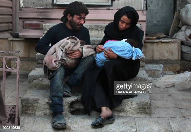 Graphic content / A Syrian man and a woman mourn over the body of one of their children in the rebelheld besieged town of Douma following air strikes...