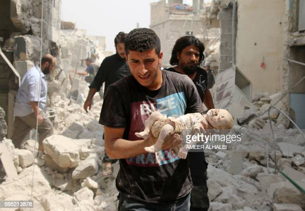 Graphic content / A Syrian man carries a dead baby in the rubble of buildings following a barrel bomb attack on the Bab alNairab neighbourhood of the...