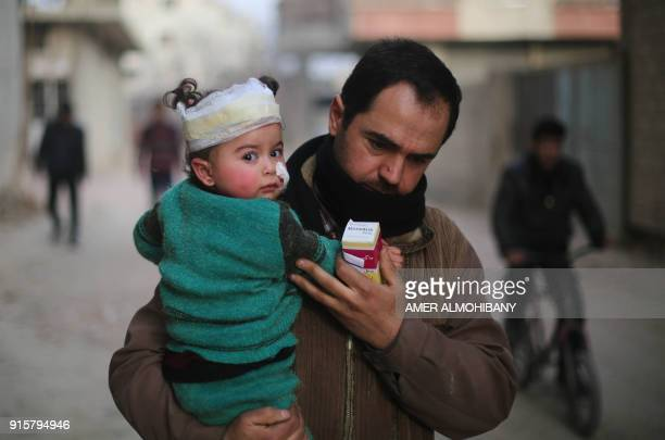 Graphic content / A Syrian man carries a wounded baby in the rebelheld enclave of Arbin in the Eastern Ghouta near Damascus following air strikes on...