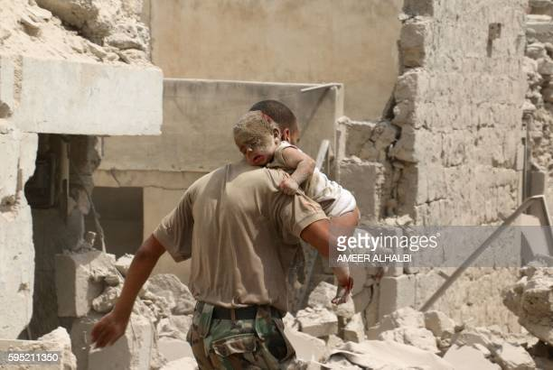 Graphic content / A Syrian man carries a wounded baby in the rubble of buildings following a barrel bomb attack on the Bab alNairab neighbourhood of...