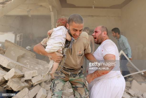 Graphic content / A Syrian man carries a wounded child following a barrel bomb attack on the Bab alNairab neighbourhood of the northern Syrian city...