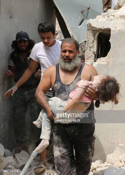 Graphic content / A Syrian man carries a wounded child in the rubble of buildings following a barrel bomb attack on the Bab alNairab neighbourhood of...