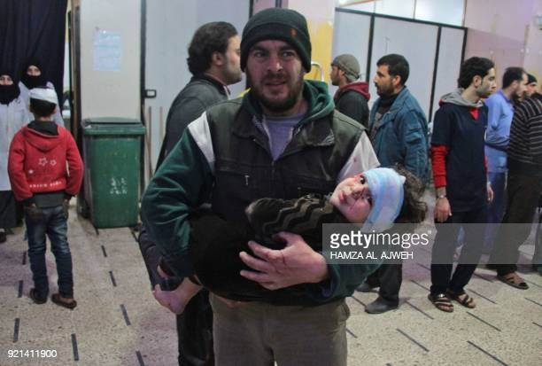 Graphic content / A Syrian man carries a wounded infant at a makeshift hospital in the rebel-held town of Douma, following air strikes by regime...