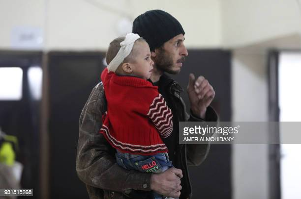 Graphic content / A Syrian man carries an injured baby into a makeshift clinic during Syrian government air strikes on Zamalka in the rebel enclave...