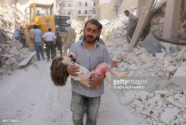 Graphic content / A Syrian man carries the body of a child following a reported Syrian government forces bombing at the Tariq alBab neighbourhood in...