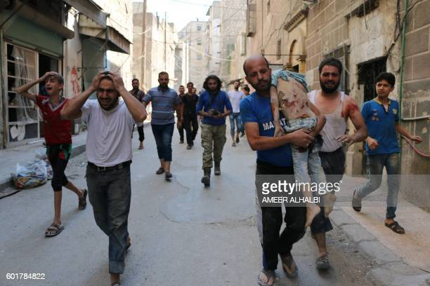 Graphic content / A Syrian man carries the body of a child following a reported air strike on the rebelheld Salihin neighbourhood of the northern...