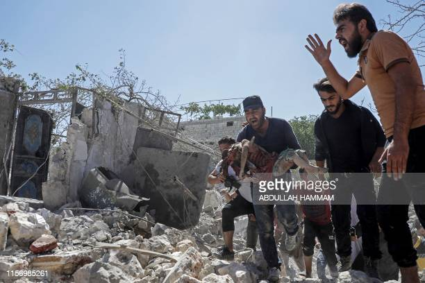 Graphic content / A Syrian man carries the body of a child killed following a reported airstrike by Syrian regime forces in Kafar Roma town in the...