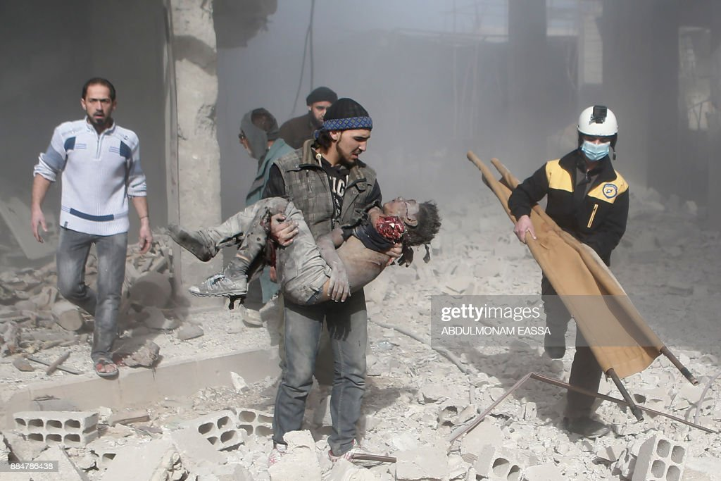 Graphic content / A Syrian man carries the body of a child who was killed in a reported air strike in the rebel-controlled town of Hamouria, in the eastern Ghouta region on the outskirts of the capital Damascus, on December 3, 2017. A wave of Syrian air strikes killed at least 19 civilians and wounded dozens across the besieged rebel enclave of Eastern Ghouta near Damascus, the Britain-based Syrian Observatory for Human Rights said. /