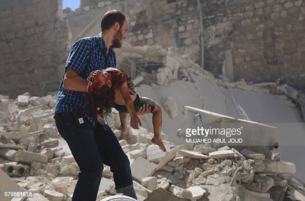 Graphic content / A Syrian man carries the body of a girl after she was trapped under the rubble following reported air strikes on the rebelheld...