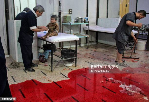 Graphic content / A Syrian man cleans a pool of blood from the floor as another one treats a baby at a makeshift clinic following reported shelling...