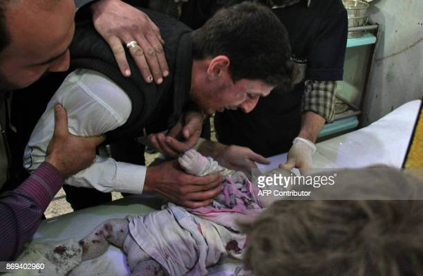 Graphic content / A Syrian man cries over a lifeless baby on November 2 2017 at a makeshift clinic in Douma in the Eastern Ghouta region outside...