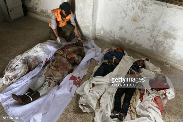 Graphic content / A Syrian man looks at the bodies of a man and three children lying on the floor at a medical centre after they were killed in...
