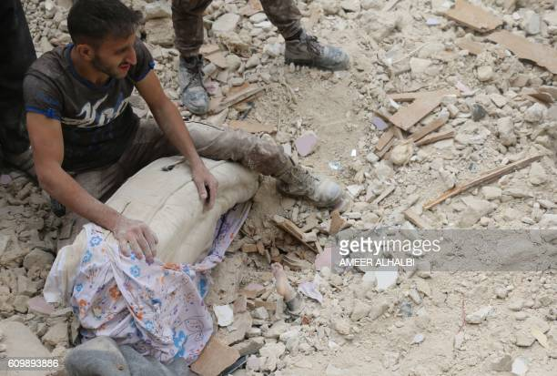 Graphic content / A Syrian man reacts next to the foot of a child sticking out out from under the rubble of a building following bombardment on the...