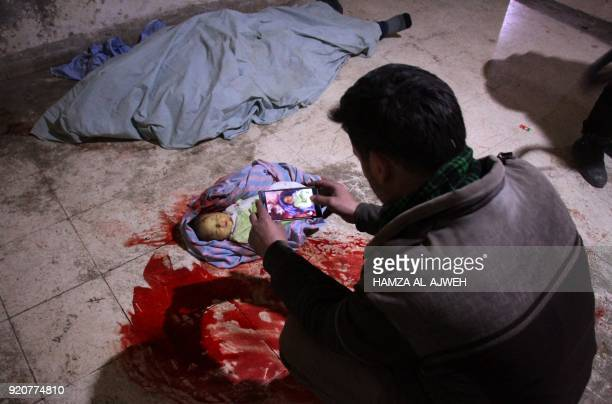 Graphic content / A Syrian man takes a picture of the body of a baby at a makeshift morgue in Douma after they were killed in air strikes on the...