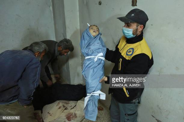 Graphic content / A Syrian medic displays the body of a child at a makeshift clinic following a suspected chemical attack on the rebelheld village of...
