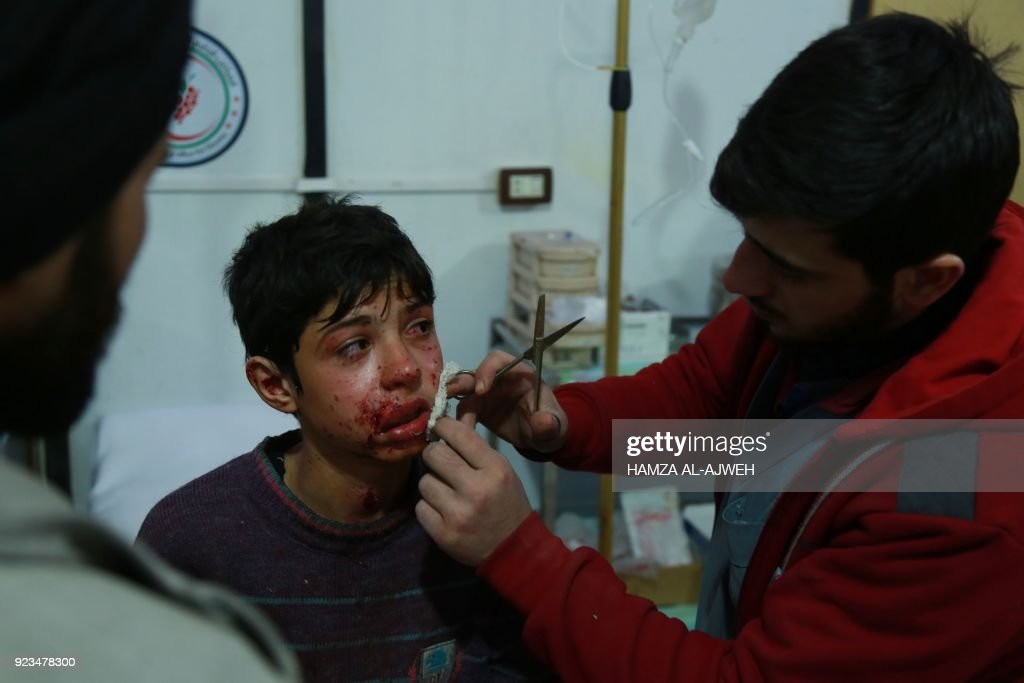 Graphic content / A Syrian medic treats a wounded boy at a makeshift hospital in the rebel-held town of Douma, in the besieged Eastern Ghouta region on the outskirts of the capital Damascus, following air strikes by regime forces on the area on February 23, 2018. Syrian regime air strikes and artillery fire hit the rebel-held enclave of Eastern Ghouta for a sixth straight day killing dozens of civilians, as the world struggled to reach a deal to stop the carnage. /