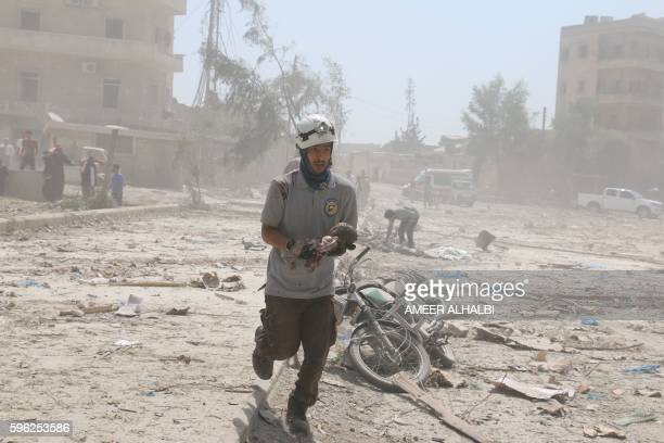 Graphic content / A Syrian rescue woker carries a dead baby in the Maadi district of eastern Aleppo after regime aircrafts reportedly dropped...