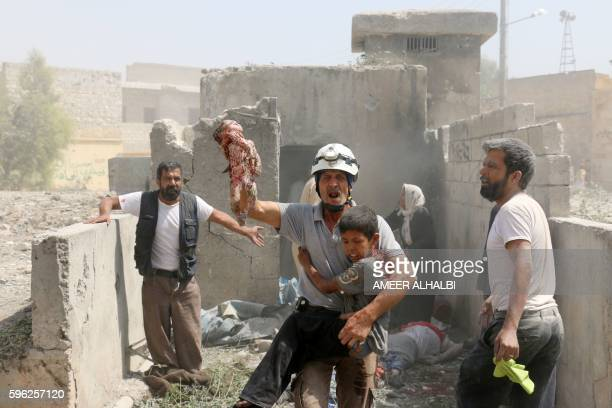 Graphic content / A Syrian rescue worker evacuates a dead baby and a wounded child as civilians search for victims in the Maadi district of eastern...