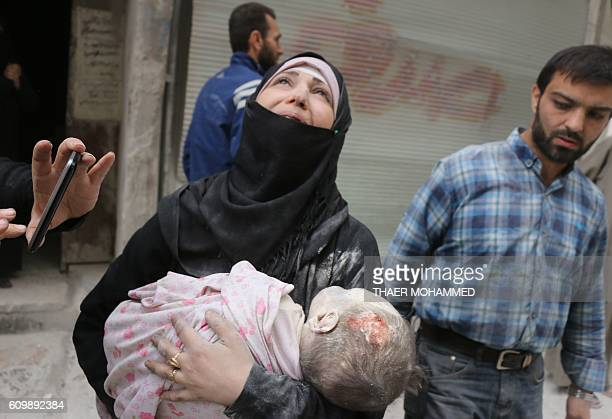 Graphic content / A Syrian woman carries the body of her infant after he was retrieved from under the rubble of a building following a reported...