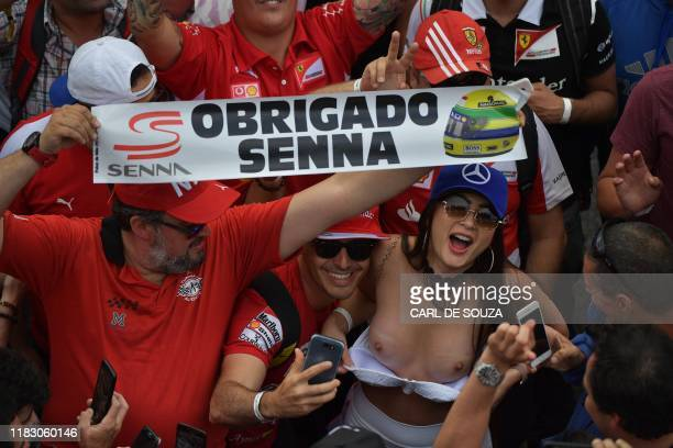 Graphic content / A topless woman and men with a sign reading Thank you Senna celebrate as Bruno Senna the nephew of late Brazilian driver Ayrton...