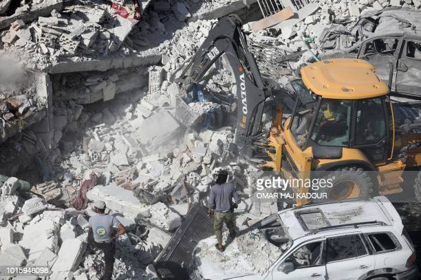 Graphic content / A tractor clears the rubble of destroyed buildings on August 12 2018 following an explosion at an arms depot in a residential area...