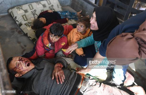 Graphic content / A truck carrying a family wounded following a Turkish airstrike on a village in the Afrin district arrives on January 28 at the...