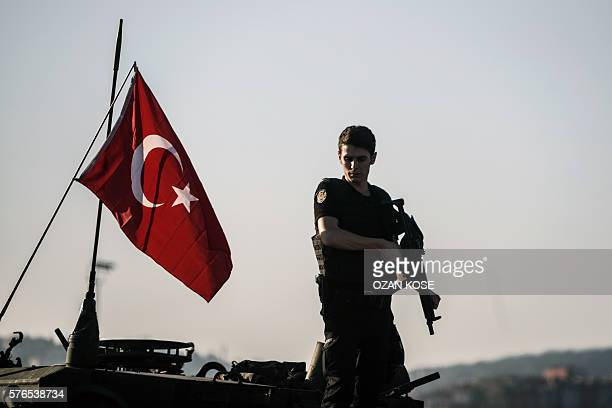 Graphic content / A Turkish anti riot police officer stands guard on a tank after a military position on the Bosphorus bridge was taken over in...