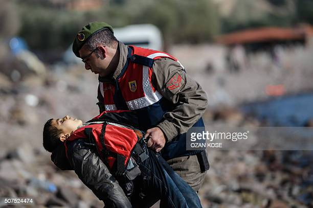 Graphic content / A Turkish gendarme carries the body of a child on a beach in Canakkale's Bademli district on January 30 2016 after at least 33...