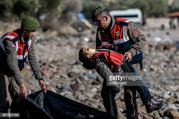 Graphic content / A Turkish gendarme carries the body of a migrant child on beach in Canakkale's Bademli district on January 30 2016 after at least...