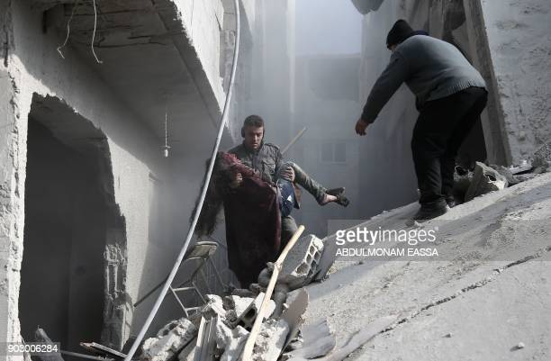 Graphic content / A volunteer from the Syrian Civil Defence carries a wounded girl after digging her out of the rubble following an air strike on...