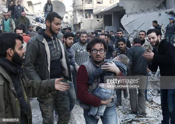Graphic content / A volunteer from the Syrian Civil Defence carries an infant after digging him out of the rubble following an air strike on Hamouria...