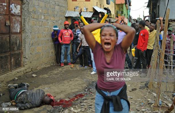 Graphic content / A woman claiming to be the sister of a man allegedly shot dead by Kenyan police and lying on the ground reacts in a street of...