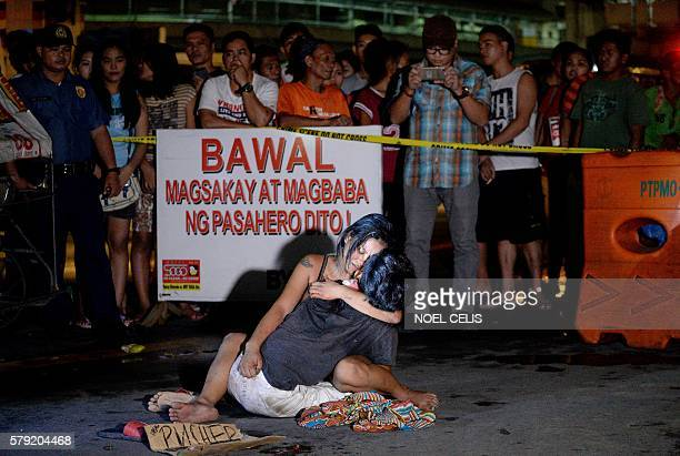 Graphic content / A woman hugs her husband next to a placard which reads 'I'm a pusher' who was shot dead by an unidentified gunman in Manila on July...