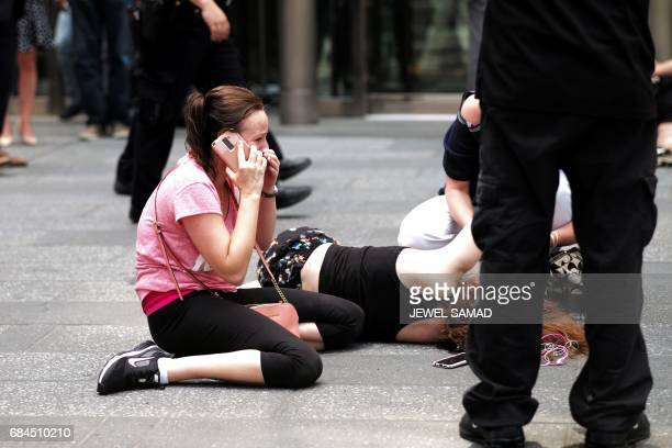 Graphic content / A woman makes a phone call as others attend to an injured person after a car plunged into them in Times Square in New York on May...