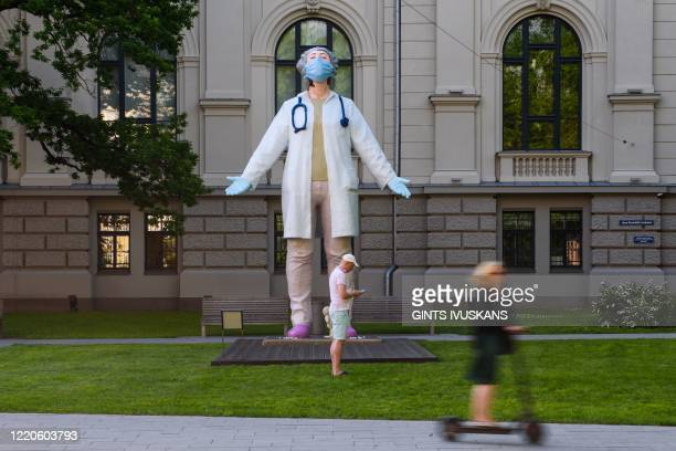 Graphic content / A woman on a scooter drives past a 6 meters high statue of a female doctor by Latvian artist Aigars Bikse called Medics to the...