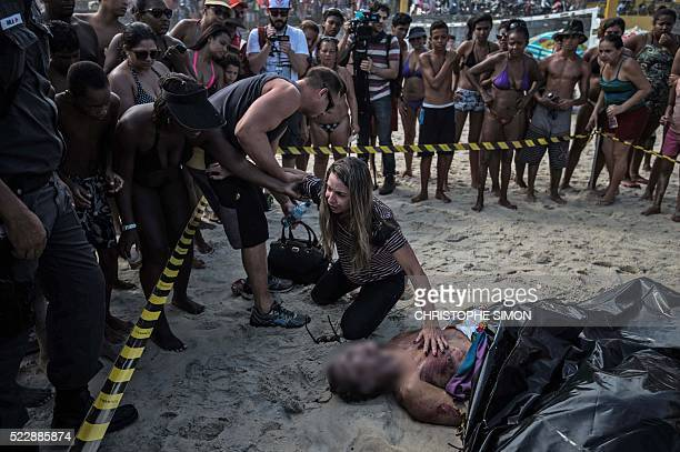 Graphic content / A woman remains next to her husband's corpse after the collapse of a recently inaugurated bicycle track in Rio de Janeiro Brazil on...