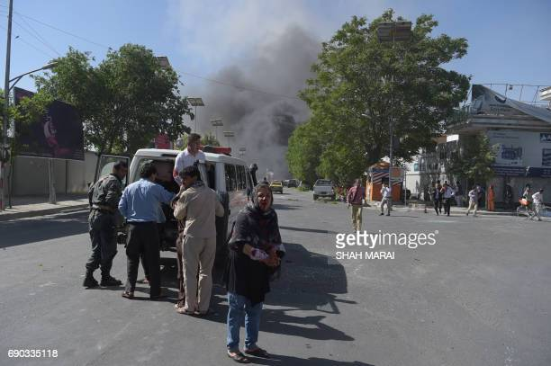 Graphic content / A wounded Afghan woman looks on after receiving first aid at the site of a car bomb attack in Kabul on May 31 2017 A massive blast...