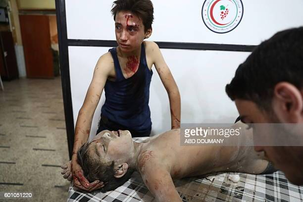 Graphic content / A wounded Syrian boy comforts another young victim at a makeshift hospital following reported government air strikes on the...