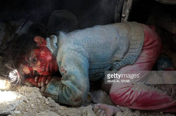 Graphic content / A wounded Syrian girl awaits rescue from under the rubble next to the body of her sister who did not survive regime bombardment in...