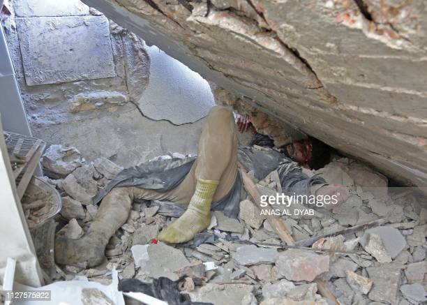 Graphic content / A wounded Syrian man awaits rescue from under the rubble of a building following reported shelling in the town of Khan Sheikhun in...