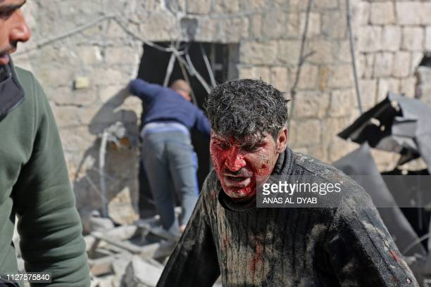 Graphic content / A wounded Syrian man reacts after following reported shelling in the town of Khan Sheikhun in the southern countryside of the...